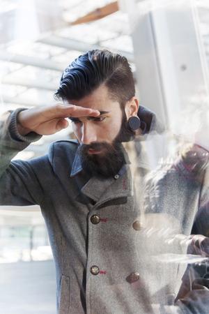 through window: businessman looking through window Stock Photo