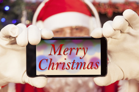 funny bearded man: santa claus shows a christmas card on a smart phone display