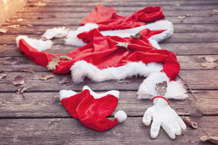 funny bearded man: santa suit abandoned on a wooden floor