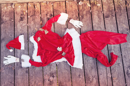 funny bearded man: santa suit abandoned on a wooden floor warm look colored