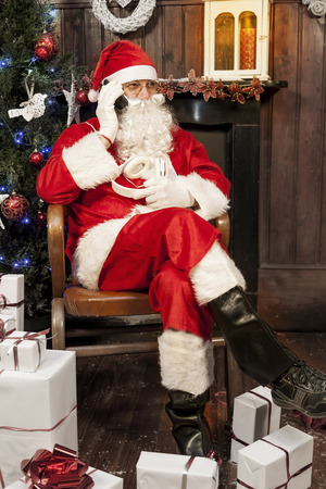old man: santa claus talking to smart phone sitting in armchair at his home Stock Photo