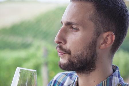 hombre barba: hombre con barba y guapo mirando copa de vino antes de beber