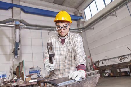 anvil: metalworker works metal with hammer on the anvil