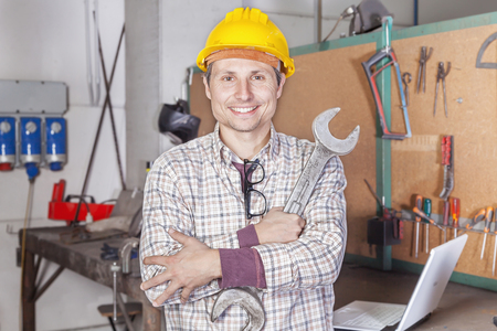 metalworker: portrait of young metalworker arms folded with wrench