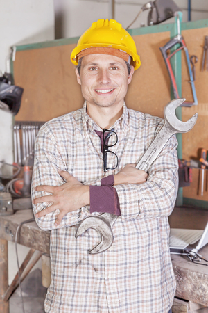 portrait of young metalworker arms folded with wrench