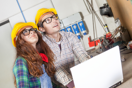 taskmaster: couple of engineers consult the computer in a steel mill