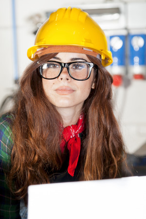 taskmaster: portrait of pretty engineer consult the computer in a steel mill