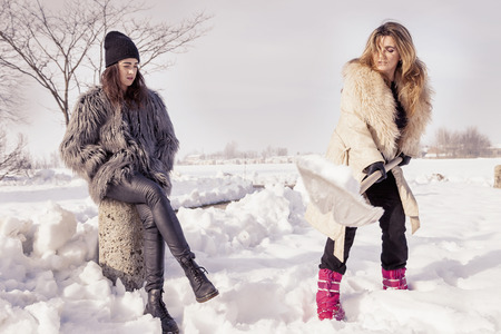 femme blonde: young women shoveling snow near a small wood Banque d'images