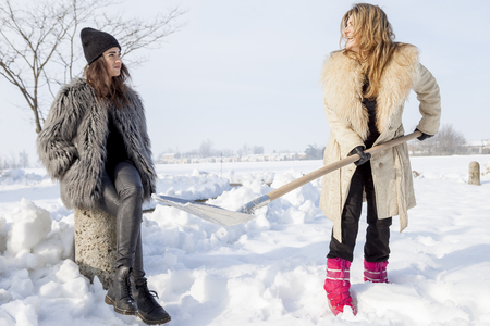 belle brunette: jeunes femmes pelleter de la neige pr�s d'un petit bois Banque d'images