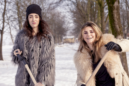shoveling: young women shoveling snow near a small wood Stock Photo