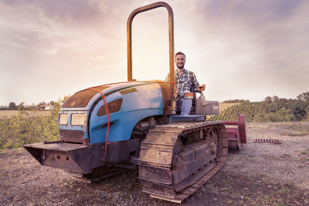 glass cutter: young farmer toasts on a crawler tractor in his vineyard Stock Photo