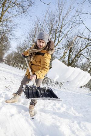 shoveling: young man shoveling snow near a small wood