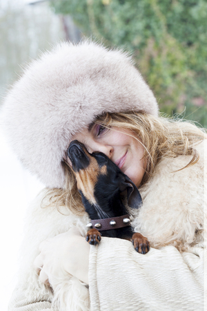 cuddle: pretty lady cuddle her little dog in winter time