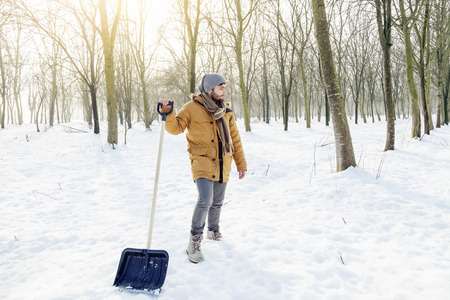 active adult community: young man shoveling snow near a small wood