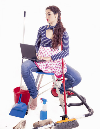 charlady: pretty young housewife consult your laptop in a break Stock Photo