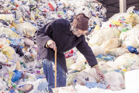 hobo: homeless man digs in the garbage