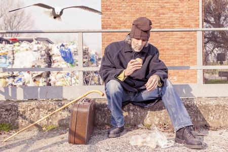 landfills: tramp eating bread sitting in landfills