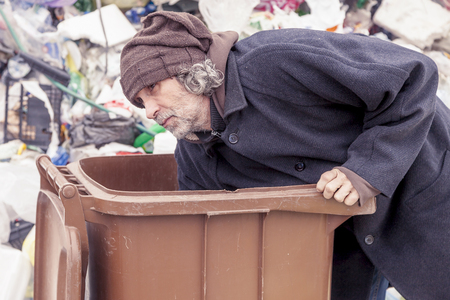 landfill: homeless rummages in the dustbin of landfill