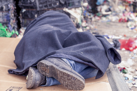 vagabond: homeless man sleeps in the waste on a wire mesh of bed