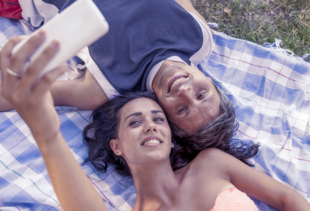 cool people: young couple lying on cloth take a selfie lying in the park Stock Photo