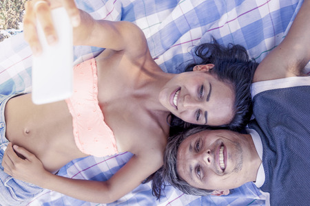 pic nic: young couple lying on cloth take a selfie lying in the park Stock Photo