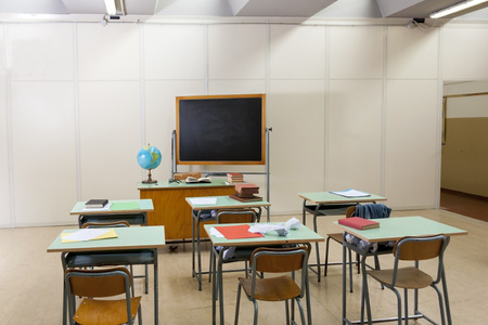 desks and blackboard in classroom at school Stock Photo