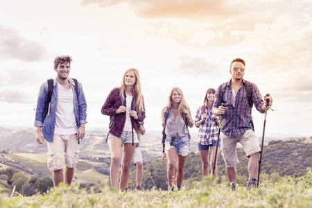 healthy sport: group of young hikers looks to the horizon over the mountain