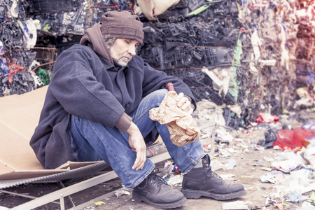 landfill: homeless man with a bottle of red wine in landfill Stock Photo