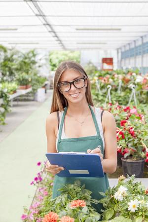 flower seller: pretty young flower seller checks his folder Stock Photo