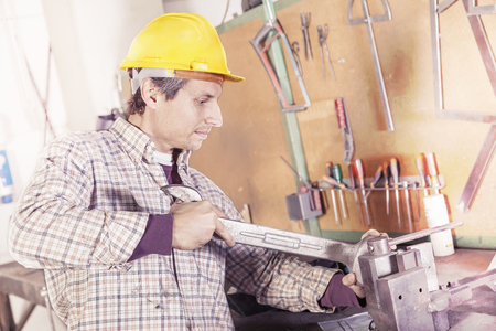 taskmaster: portrait of young metalworker engaged with wrench