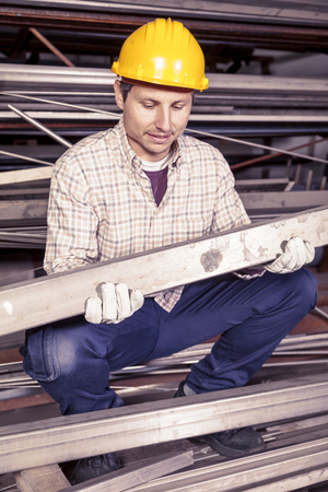 steel mill: young metalworker controls some metal bars in steel mill Stock Photo