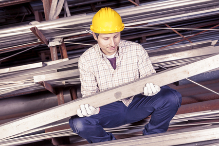 metalworker: young metalworker controls some metal bars in steel mill Stock Photo