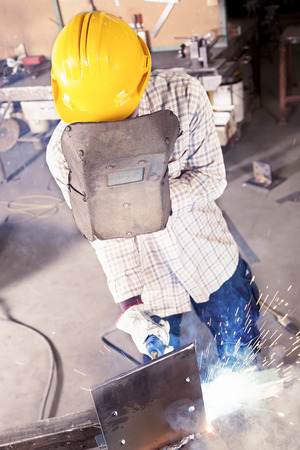 steel mill: young worker while welding in a steel mill
