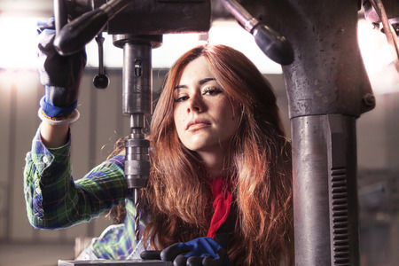 taskmaster: portrait of pretty girl at work on industrial drilling machine Stock Photo