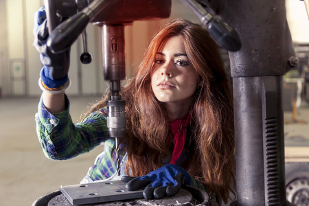 drilling machine: portrait of pretty girl at work on industrial drilling machine Stock Photo