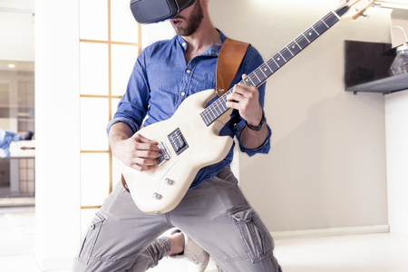 viewer: young adult playing guitar at home using viewer for augmented reality