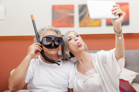 diving mask: mature happy couple takes a selfie joking in hotel room wearing a diving mask