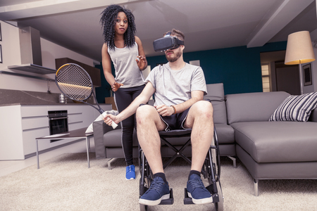 young girl helps a disabled who plays tennis with augmented reality
