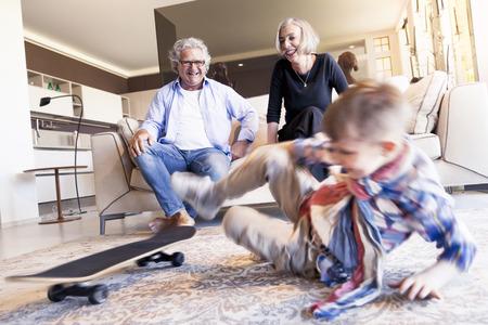 nephew: couple of happy grandparents are fun nephew with skateboard Stock Photo