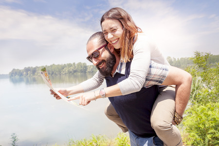 funny bearded man: young couple of lovers consults a map