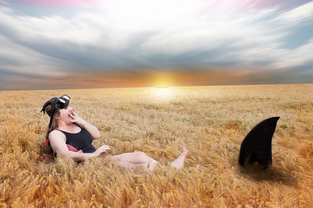 encounter: woman has a close encounter with a shark in a field of wheat. surreal image