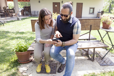 funny bearded man: young couple of lovers consults smart phone outdoor