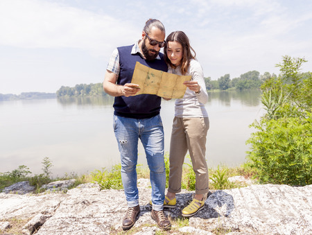 funny bearded man: young couple of lovers consults a map outdoor Stock Photo