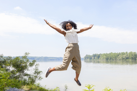 young girl jumps on the bank of a river