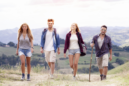 group of young hikers walking toward the horizon over the mountain Stock Photo