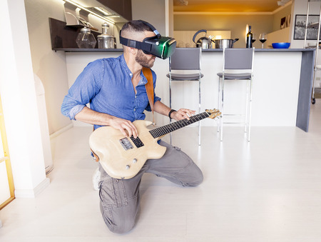 viewer: young adult playing guitar at home using viewer for virtual reality