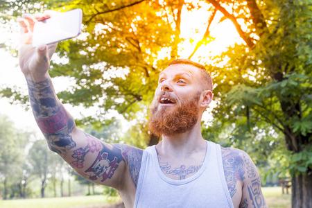 hombre barba: hombre de la barba tatuada toma una autofoto en el parque Foto de archivo