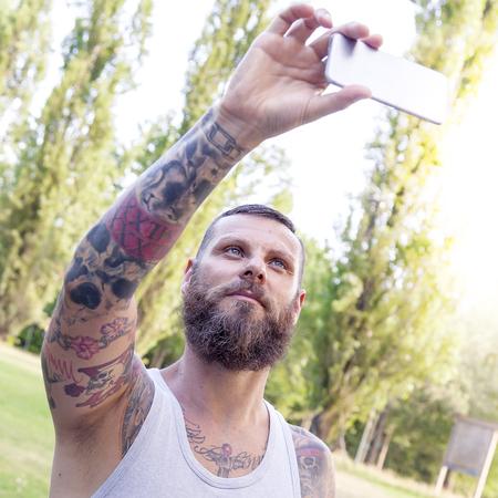 hombre con barba: hombre de la barba tatuada toma una autofoto en el parque Foto de archivo