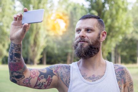 hombre barba: tattooed bearded man takes a selfie in the park Foto de archivo