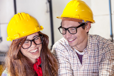 taskmaster: couple of engineers having fun consult the computer in a steel mill Stock Photo